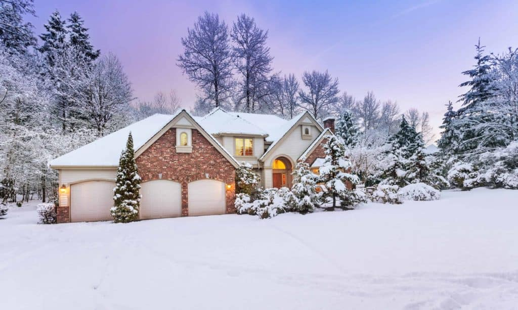 Driveway view of snowy home – daylight fades over a snow-covered